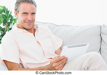 vrolijk, man, op, zijn, bankstel, gebruik, tablet pc, kijken naar van fototoestel
