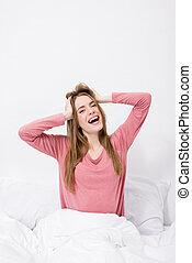 vrolijk, vrouw stretching, in bed