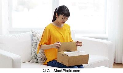 vrolijke , aziaat, jonge vrouw , met, pakket, doosje, thuis