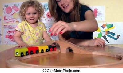 vrolijke , babysitter, en, toddler, kind, meisje, spel met, houten trein, in, kleuterschool