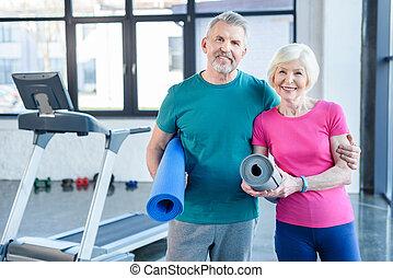 vrolijke , fitness, paar, vasthouden, yoga matten, en, het glimlachen, aan fototoestel, in, gym