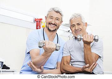vrolijke , fysiotherapeut, en, senior, patiënt, het tilen, dumbbells