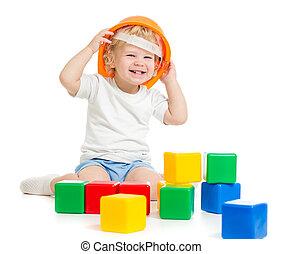 vrolijke , geitje, jongen, in, harde hoed, spelend, met, kleurrijke, bouwstenen, vrijstaand, op wit