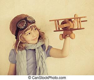 vrolijke , geitje, spelend, met, het vliegtuig van het stuk speelgoed