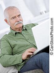 vrolijke , hogere mens, gebruikende laptop, thuis
