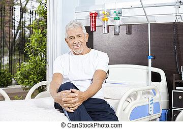 vrolijke , hogere mens, zitting op het bed, op, rehabilitatie, centrum