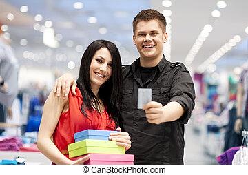 vrolijke , jong paar, bestedend geld, op, de opslag van de kleding