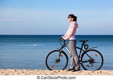 vrolijke , jonge, aantrekkelijk, vrouw ontspannend, op, de, fiets, uitstapjes, op, de, strand.