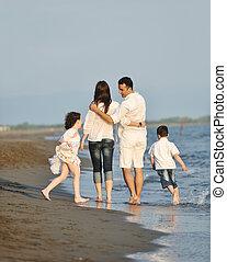 vrolijke , jonge familie, hebben vermaak, op, strand, op, ondergaande zon