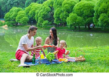 vrolijke , jonge familie, picnicking, buitenshuis