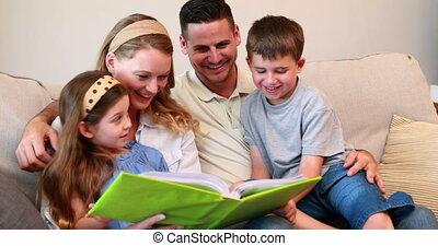vrolijke , jonge familie, zitten op sofa