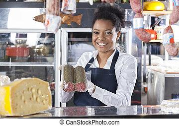 vrolijke , jonge, verkoopster, het tonen, kaas, op, toonbank