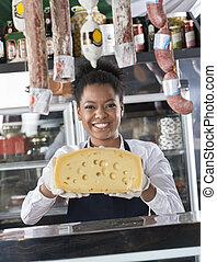 vrolijke , jonge, verkoopster, vasthouden, kaas, op, toonbank