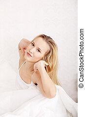 vrolijke , jonge vrouw , stretching, in bed
