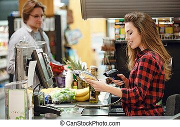 vrolijke , kassier, vrouw, op, werkruimte, in, supermarkt, winkel