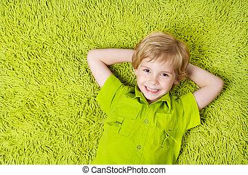 vrolijke , kind, het liggen, op, de, groene, tapijt,...