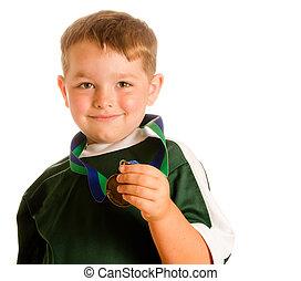 vrolijke , kind, in, voetbal, of, voetbal tenue, met, medaille, vrijstaand, op wit