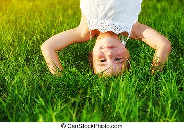 vrolijke , kind, meisje, staand, ondersteboven, op, zijn, hoofd, gras, in, zomer