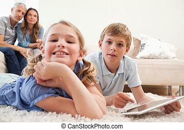 vrolijke , kinderen, gebruik, een, tablet, computer, met, hun, ouders, op, de, achtergrond, in, een, woonkamer