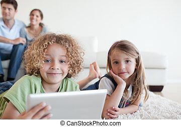 vrolijke , kinderen, gebruik, een, tablet, computer, terwijl, hun, vrolijke , ouders, zijn, schouwend, in, hun, woonkamer