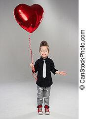 vrolijke , kleine, jongen, met, rood hart, balloon, op, een, licht, achtergrond