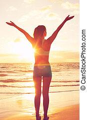 vrolijke , kosteloos, vrouw, op, ondergaande zon , op het strand