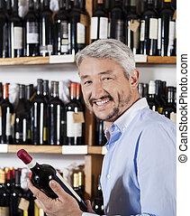 vrolijke , mannelijke , klant, vasthouden, wijn fles, in, supermarkt