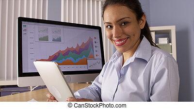 vrolijke , mexicaanse , businesswoman, zitting op het bureau