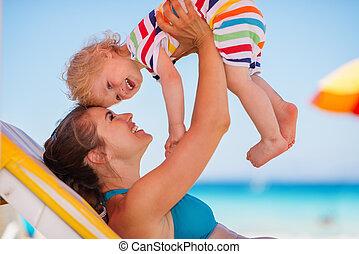vrolijke , moeder het spelen, met, baby, op, zonnebank