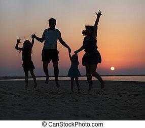 vrolijke , mooi, gezin, springt, op het strand, op, de, ondergaande zon
