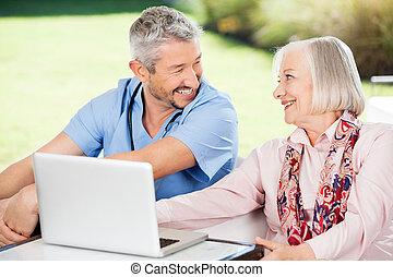 vrolijke , oude vrouw, en, huisbewaarder, met, draagbare computer, op, portiek