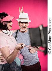 vrolijke , oude vrouw, kijken naar, echtgenoot, terwijl, boeiend, selfie, samen, vrijstaand, op, roze