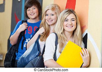 vrolijke , scholieren, leunend, schoolmuur