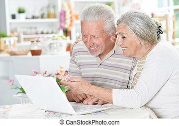 vrolijke , senior koppel, gebruikende laptop