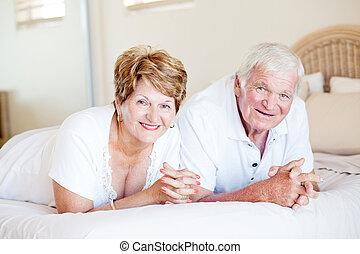 vrolijke , senior koppel, het liggen op het bed