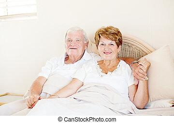 vrolijke , senior koppel, holdingshanden, in bed