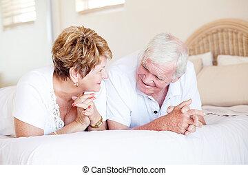 vrolijke , senior koppel, kletsende, op bed