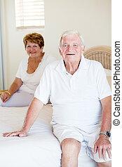 vrolijke , senior koppel, zitting op het bed