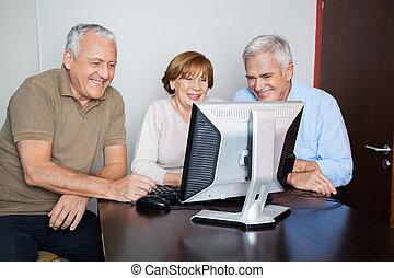 vrolijke , senior, mensen, het gebruiken computer, op het bureau