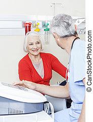 vrolijke , senior, patiënt, kijken naar, mannelijke , fysiotherapeut, gebruik, machi