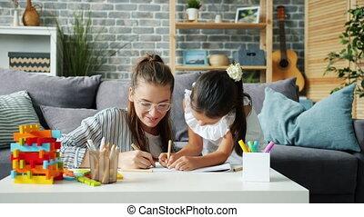 vrolijke , tekening, hebben, meisje, gebruik, potloden, moeder, het geven, weinig; niet zo(veel), thuis, plezier