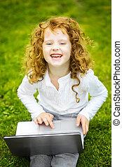 vrolijke , verwonderd, kind, met, draagbare computer, zittende , op, de, grass.