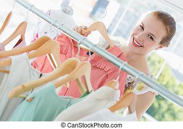 vrolijke , vrouwlijk, klant, het selecteren, kleren, in, winkel