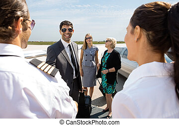 vrolijke , zakenman, met, collega's, groet, piloot, en, airhostess, op, vliegterminal