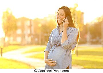vrolijke , zwangere vrouw, het spreken op de telefoon, op, ondergaande zon