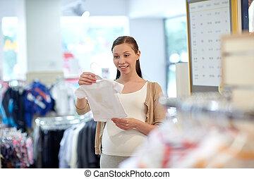 vrolijke , zwangere vrouw, shoppen , op, de opslag van de kleding