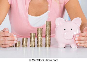 vrouw, beschermen, piggybank, met, stapel muntstukken