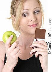 vrouw, beslissen, whether, om te eten, appel, of, chocolade