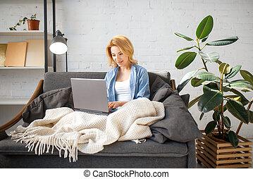 vrouw, deken, jonge, bankstel, onder, gebruikende laptop