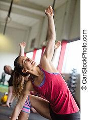vrouw, doen, uitrekkende oefening, in, fitnessclub